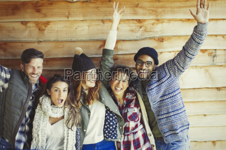 portrait playful friends cheering outside cabin