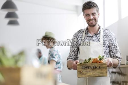 portrait smiling man holding fresh vegetables