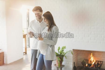 pregnant couple using digital tablet near
