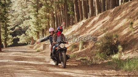 exuberant young woman riding motorcycle on