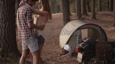 affectionate young couple hugging outside tent
