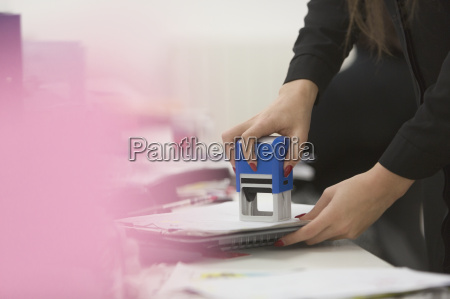 businesswoman using stamp on paperwork in