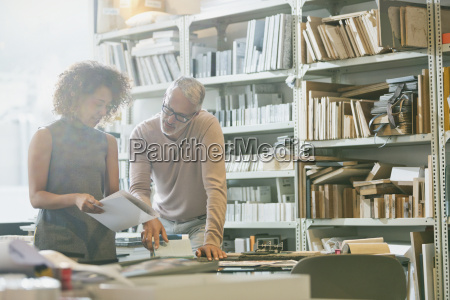 businessman and businesswoman discussing paperwork in
