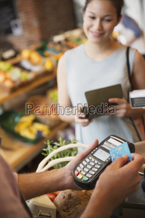 woman watching grocery store clerk using