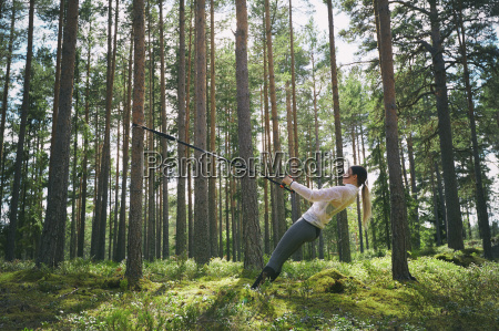 runner using resistance band on tree