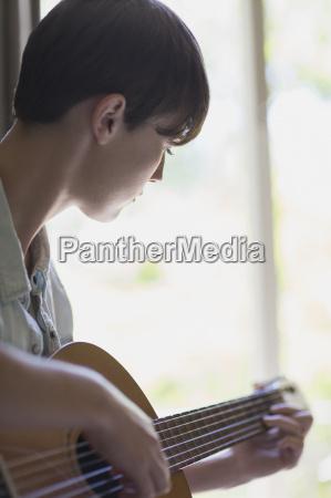 close up woman playing guitar