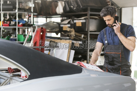 mechanic talking on cell phone ordering
