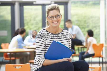 female tutor sitting in classroom with