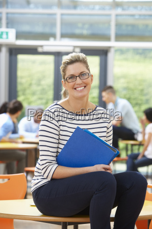 female, tutor, sitting, in, classroom, with - 19407678
