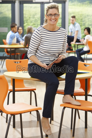 female, tutor, sitting, in, classroom, with - 19407702