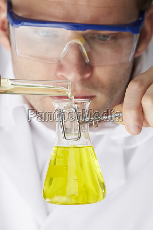 scientist pouring liquid from test tube