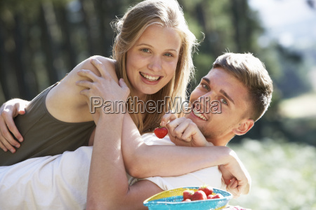 young couple enjoying picnic in countryside