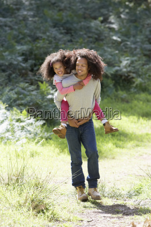 father giving daughter ride on shoulders