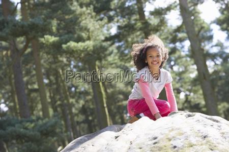 girl climbing on rock in countryside