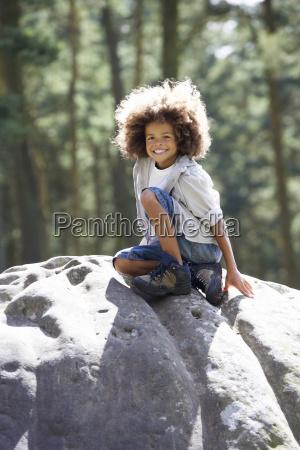 boy climbing on rock in countryside