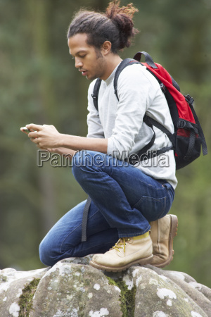man using mobile phone whilst hiking