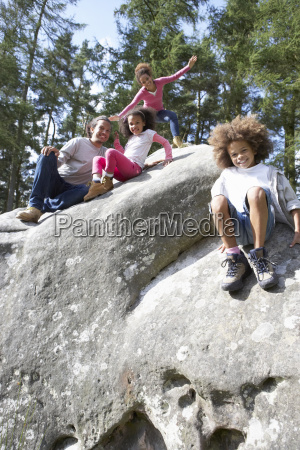 family, group, sitting, on, rock, together - 19408964
