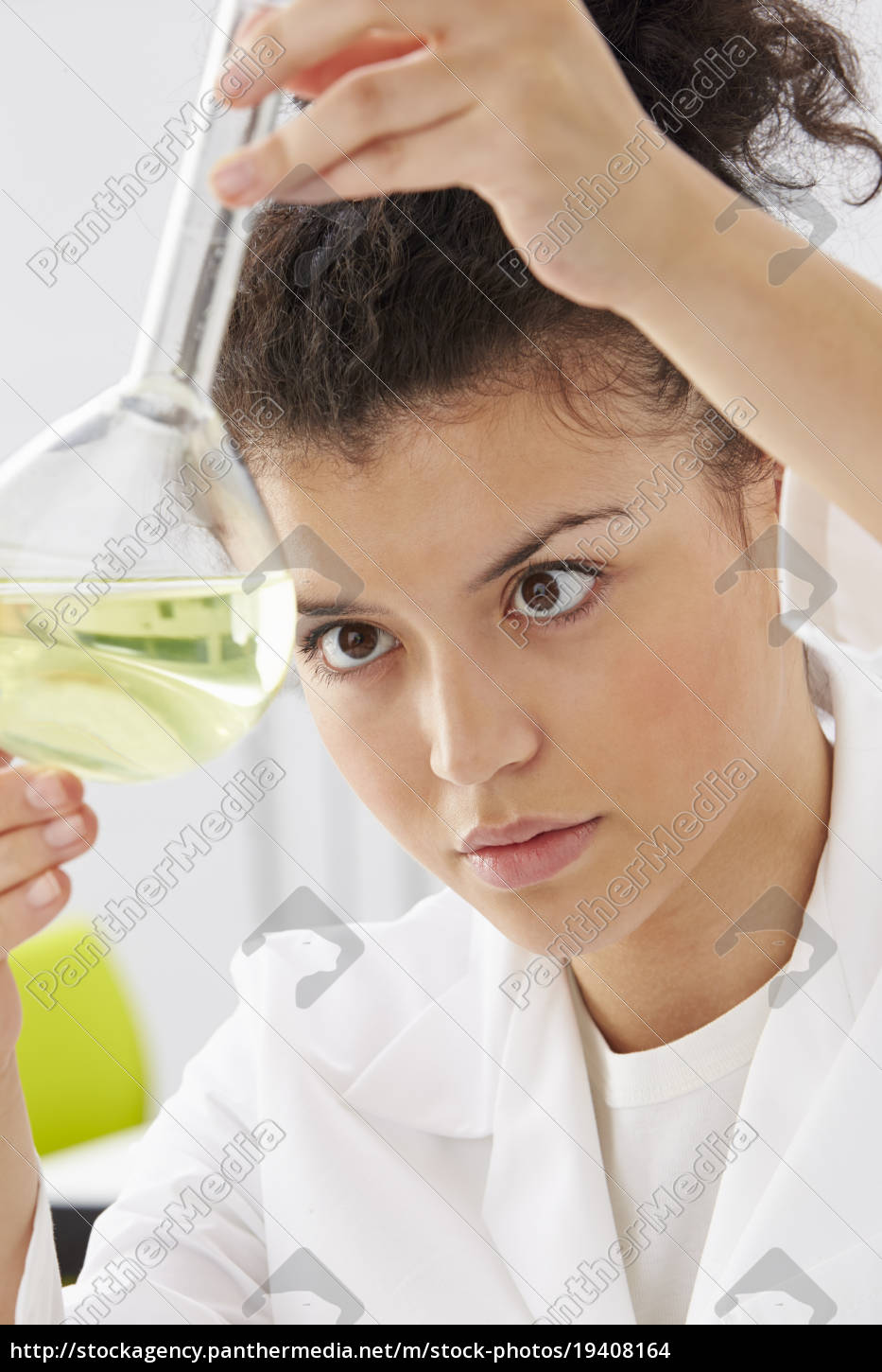 female, scientist, studying, liquid, in, flask - 19408164