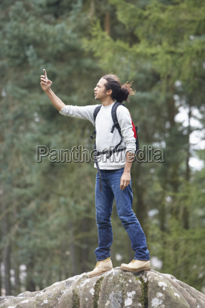 man, using, mobile, phone, whilst, hiking - 19408942
