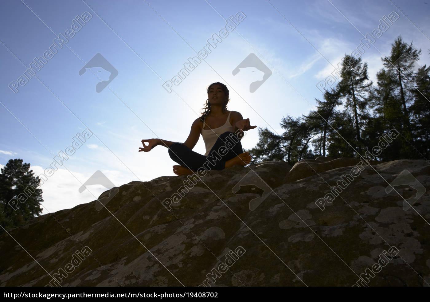 silhouette, of, teenage, girl, meditating, outdoors - 19408702