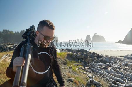 male photographer carrying tripod on coast