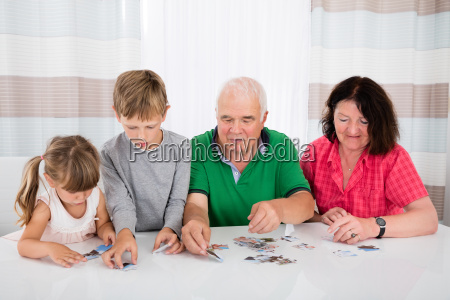 multi generation family solving puzzle together