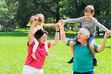 happy grandparents giving grandchildren piggyback ride