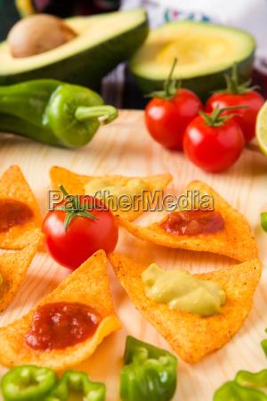 close up of nachos chips tomato