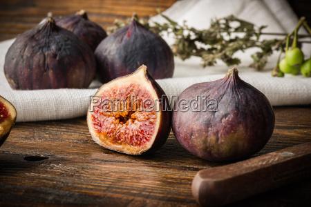 ripe purple figs on wooden table