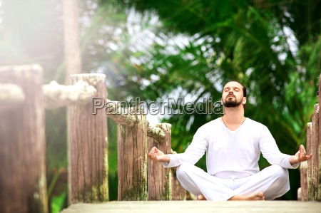 man doing yoga in tropic jungle