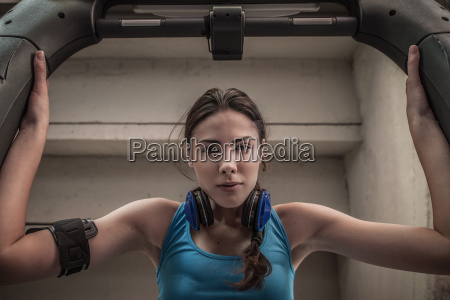 young woman using gym equipment portrait