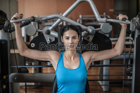 young woman using weight equipment