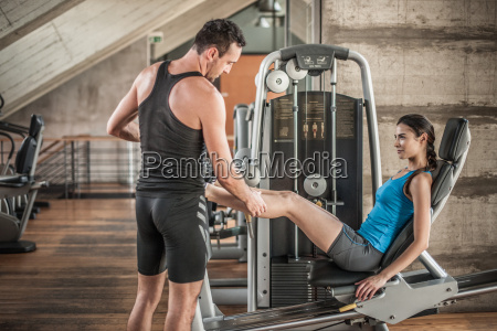 personal trainer with woman using weight