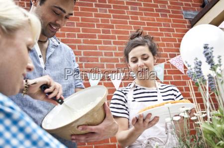 three friends preparing fruit flan and