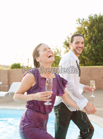 couple exiting swimming pool dressed