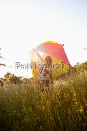 boy with kite on grassland
