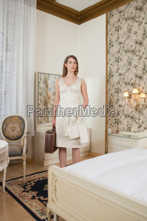 young woman with case in hotel
