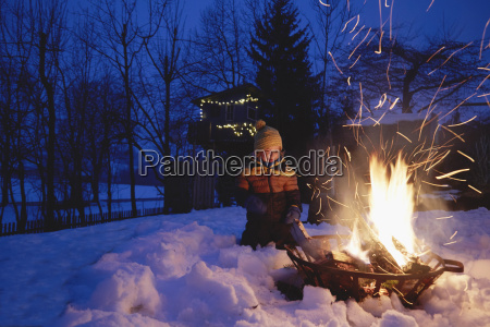 young boy sitting by fire in