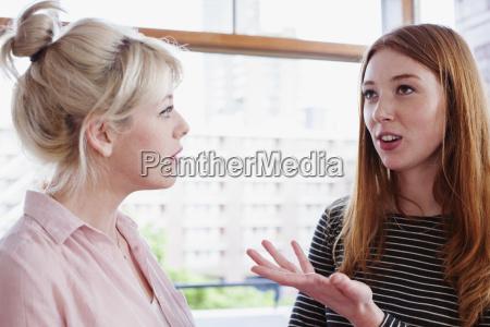 young women having conversation gesturing