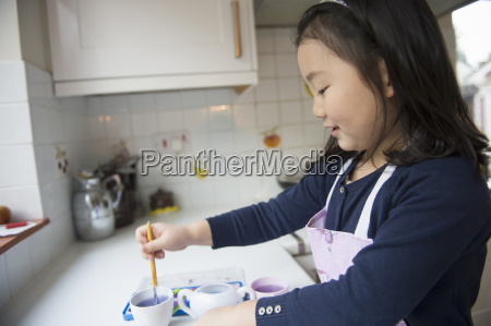 young girl dipping paintbrush in water