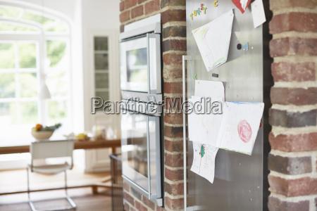 childrens drawings stuck on fridge door