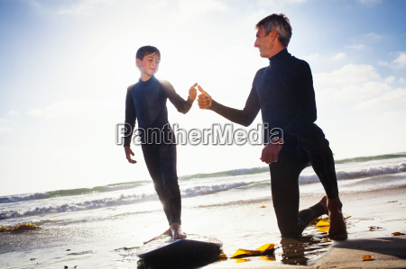 father and son with surfboard on