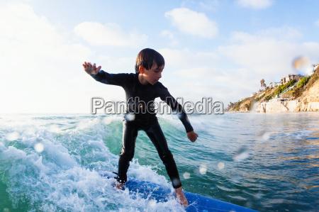 young boy surfing wave encinitas california