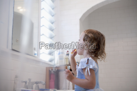 female toddler cleaning teeth