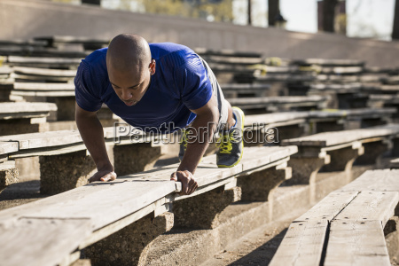 man doing push ups on bench