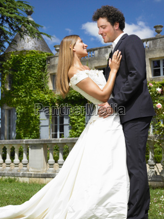 newlyweds in front of castle