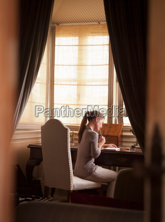 woman writing at desk in study