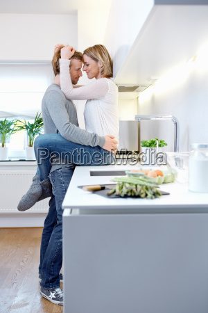 couple hugging in kitchen woman sitting