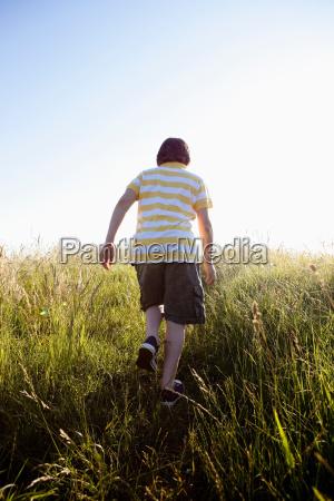 boy walking through grassland