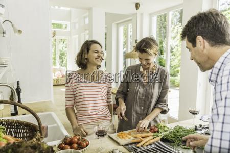 three adults chatting whilst preparing fresh
